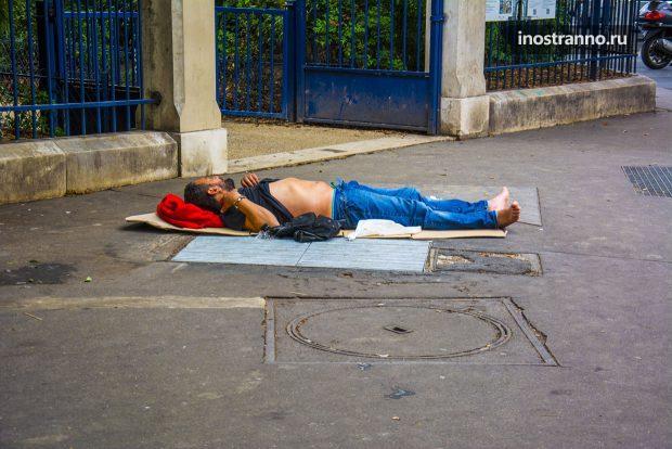 Бомж клошара спит на улице в Париже